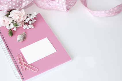 A white background styled desktop with pink paper clips, journal, notebook, ribbon, flowers, and a seashell.